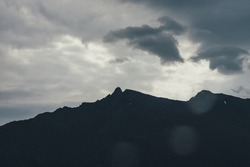 Dark atmospheric landscape with black silhouettes of mountains under gray cloudy sky in rainy weather. Gloomy mountain scenery with rainy clouds above mountain silhouette. Dark peak under rainy clouds