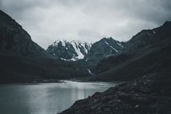Dark atmospheric landscape with mountain lake among deep black rocks on background of snowy mountains under gray cloudy sky. Bleak view to mountain lake and glacier in deep black colors. Dark tones.