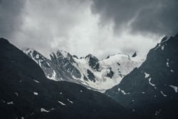 Dark atmospheric mountain landscape with glacier on black rocks in lead gray cloudy sky. Snowy mountains in gray low clouds in rainy weather. Gloomy mountain landscape with rocky mountains with snow.