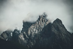 Dark atmospheric surreal landscape with dark rocky mountain top in low clouds in gray cloudy sky. Gray low cloud on high pinnacle. High black rock with snow in low clouds. Surrealist gloomy mountains.