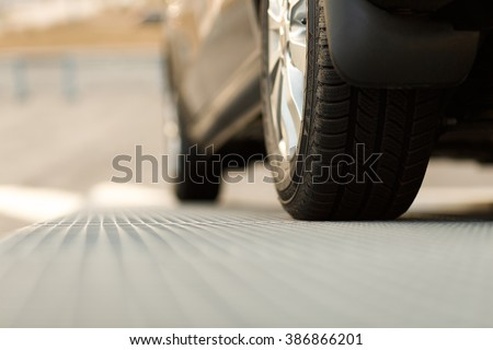 Dark automobile standing on steel floor view from below. Car parking problems, motor show or exhibition, winter season tires, customer purpose loan, vehicles official checkup or examination concept