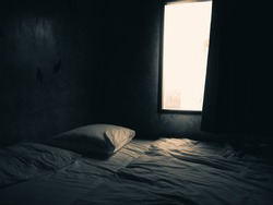 Dark bedroom with light from the window.