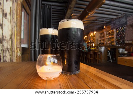 Dark beer and candle in pub setting Stock photo ©
