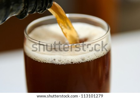 dark beer is pouring into a glass, close up