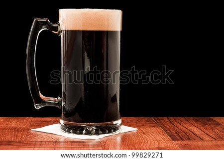 dark beer isolated on a black background served in a chilled mug
