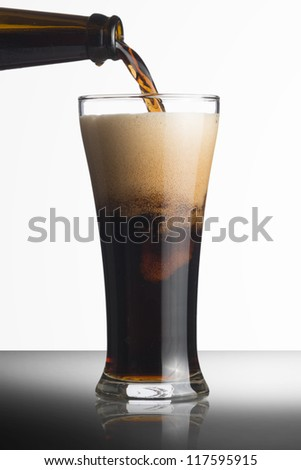 Dark beer pour from bottle to glass on white background