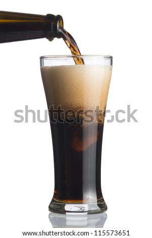 Dark beer pouring from bottle to glass isolated on white