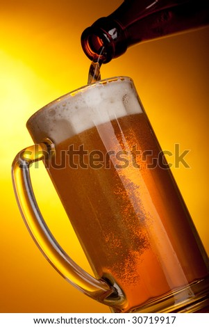 Dark beer pouring into mug on a yellow background.