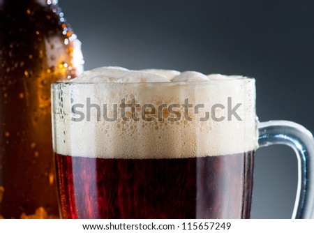 Dark beer with froth in the mug