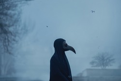 Dark black figure of a man in a mask of plague doctor stands in fog twightlight