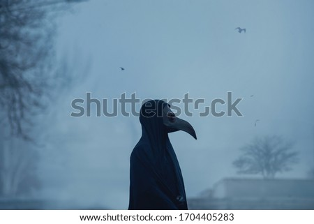 Dark black figure of a man in a mask of plague doctor stands in fog twightlight Stockfoto ©