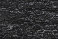 Dark black old medieval natural stone wall. Texture, background or wallpaper
