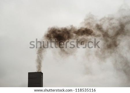 Dark black smoke from the chimney on a cold, cloudy day.