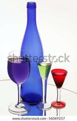 Dark blue bottle and three wine-glasses - stock photo