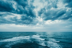 Dark blue clouds and sea or ocean water surface with foam waves before storm, dramatic seascape