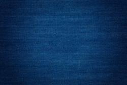 Dark blue denim background, detailed texture with vignette