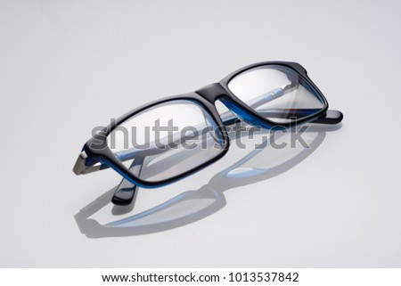 dark blue glasses on a white specular background