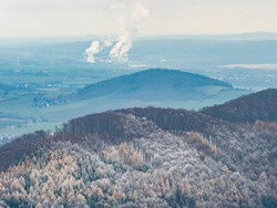 Dark blue hills with hoarfrost cover and coal power plant Turow in Poland smoking at horizon. Misty daybreak, far chimneys let out pollution and peaks of hills are sticking out from foggy background