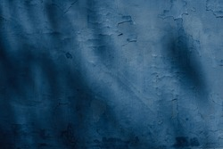 Dark blue rough surface, textured wall covered with old peeling off plaster. Texture and background photo with a spot of light and shadows
