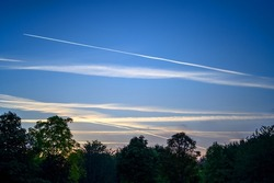 Dark blue sky at dusk with white clouds. An airplane (aeroplane) contrail extends across the sky. Silhouette of trees on the horizon. View of the sky with clouds and contrail just after sunset.