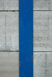 Dark blue steel plate with rust on the white concrete wall. Used as vertical background.