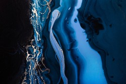 Dark blue waves in abstract ocean and golden foam. Liquid acrylic artwork with flow and splash. Marble effect background or texture