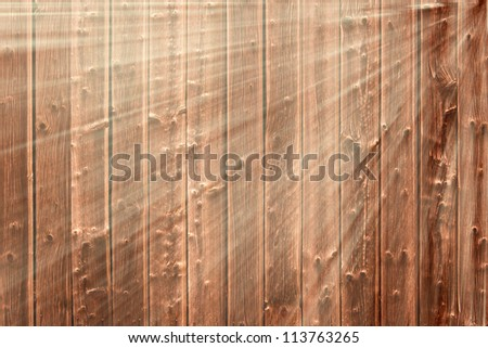 Dark brown and gnarly wooden background in sunlight