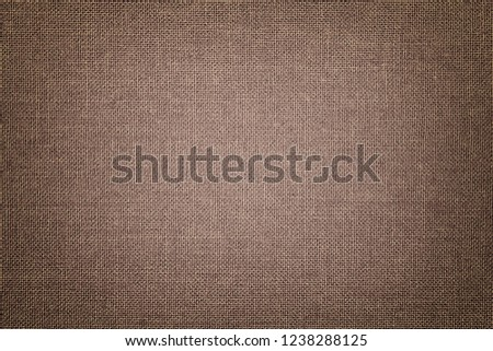 Dark brown background from a textile material with wicker pattern, closeup. Structure of the light bronze fabric with texture. Cloth backdrop with vignette. #1238288125