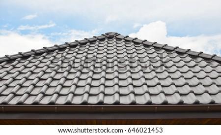 Dark brown ceramic tile roof against blue sky.