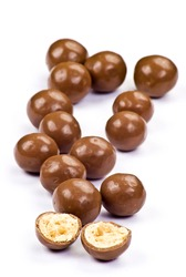 Dark brown chocolate balls and half with crisp filling over white background