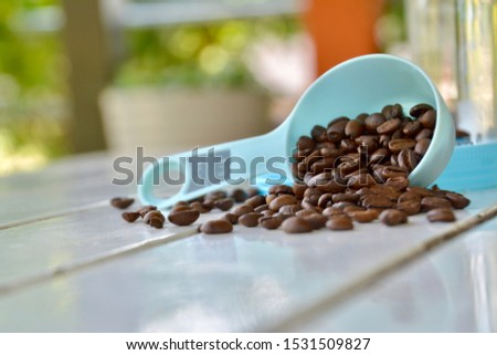 Dark brown coffee beans in a blue spoon Pour it onto the white slat table.