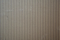Dark brown corrugated cardboard textured background with vertical ridges