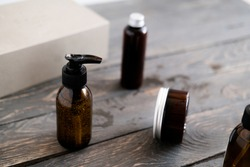 Dark brown glass cosmetic bottles on wooden table, from above. Beauty products concept