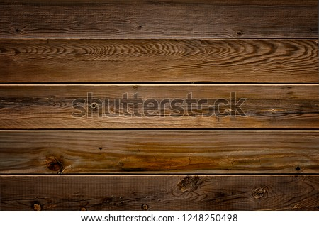 Dark brown reclaimed wood surface with aged boards lined up. Wooden planks on a wall or floor with grain and texture. Neutral stained vintage wood background. #1248250498