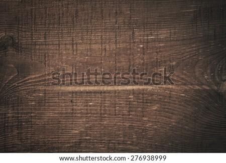 Dark brown scratched wooden cutting board. Wood texture