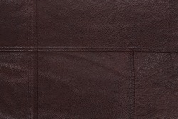 Dark brown stitched leather background. Asymmetric seams. Rough surface with free space. Expensive material sample. Handwork. Seat upholstery or leather jacket.