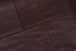 Dark brown stitched leather background. Asymmetric seams. Rough surface with free space. Expensive material sample. Handwork. Seat upholstery or leather jacket. Diagonal lines.