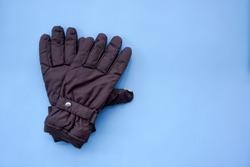 Dark Brown Winter Gloves on Blue Background Top View