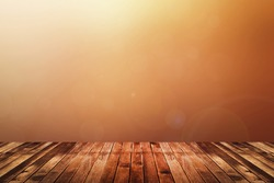 Dark brown wooden floor with abstract blurred background in warm tone color (red, orange and yellow). use for backdrop or web design