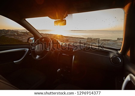 Dark car Interior - steering wheel, shift lever and dashboard. Car modern  inside. Front view on sunset and sea background. The sun shines in the glass.
