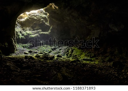 Dark cave with a bright daylight spot of exit. Natural cave opening in Crimea. Entrance to the karst cave in a mountain. Inside the subterranean cave background with copy space.