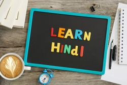 Dark chalkboard with Learn Hindi message from colourful plastic letters