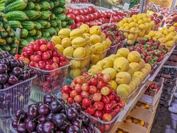 Dark cherries, cherries, apricots, strawberries and vegetables laid out on the counter of the farmers ' market. Selective focus