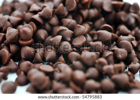 Dark chocolate chips on a white background.
