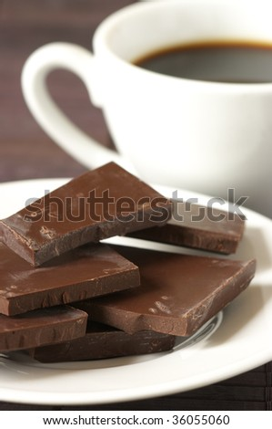 Dark chocolate close-up on white plate and white cup of coffee on brown background.