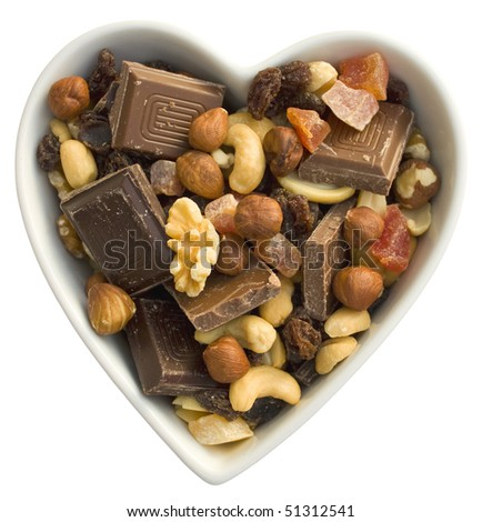 Dark chocolate, milk chocolate, dried fruits and nuts in a heart shaped bowl. Isolated on white background.