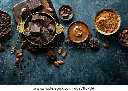 Dark chocolate pieces crushed and cocoa beans, culinary background, top view #602988734