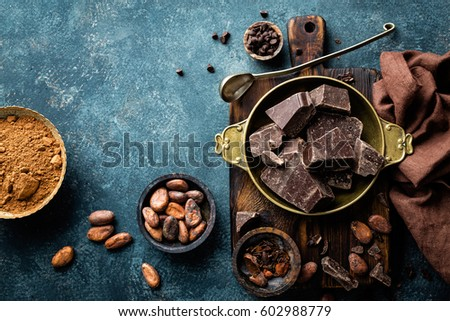 Dark chocolate pieces crushed and cocoa beans, culinary background, top view #602988779