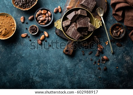 Dark chocolate pieces crushed and cocoa beans, culinary background, top view #602988917
