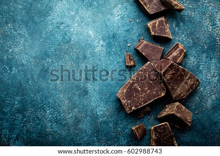 Dark chocolate pieces crushed on a dark background, view from above #602988743